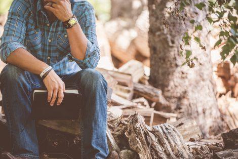 Człowiek w zadumie, siedzący na pniu